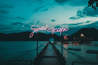 picture of pier at night with words great escape in neon over it